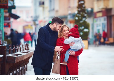 happy family, mother, father and baby walking through the winter snowy city street