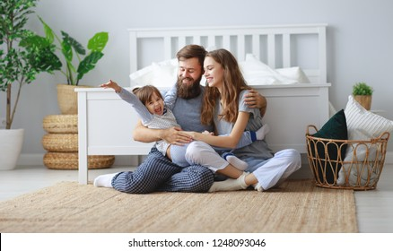 happy family mother, father and  father child daughter in bed