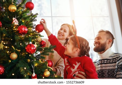 happy family mother, father and child daughter decorate Christmas tree at home