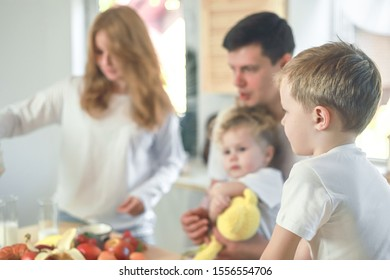 Happy family mother, father, child daughter and son having breakfast at home. Vitamine breakfast in bright kitchen room interior. Blur background.