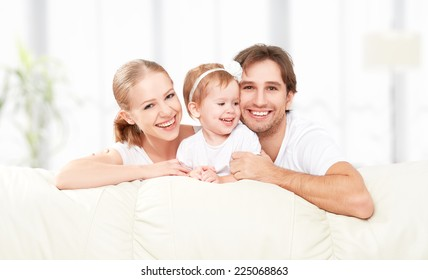 Happy family mother, father, child baby daughter at home on the sofa playing and laughing