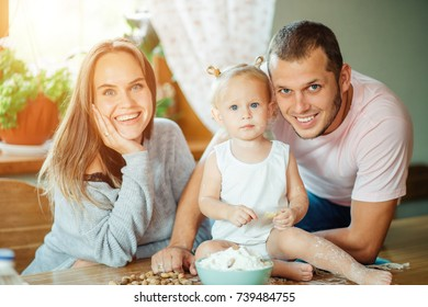 happy family mother, father, child daughter at home looking at camera.