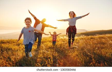 Gelukkige familie: moeder, vader, kinderen zoon en dochter op de natuur bij zonsondergang