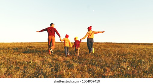 Happy family: mother, father, children son and  daughter on nature  on autumn sunset