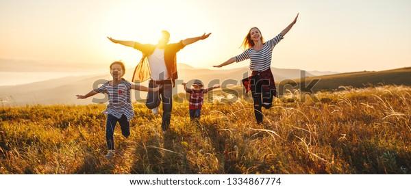 Fröhliche Familie: Mutter, Vater, Kinder Sohn und Tochter auf der Natur bei Sonnenuntergang