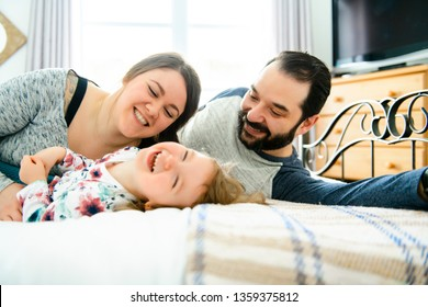 A Happy family, mother, father and daughter on the white bed
