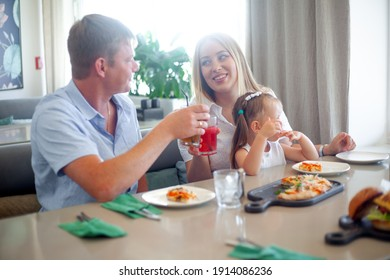 Happy family mother father and daughter sitting in cafe and take italian food, people testing pizza and drink juice