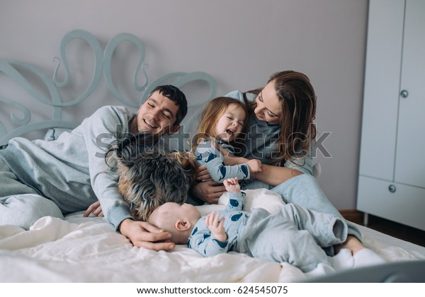 Happy family - mother, father, daughter and baby on the bed