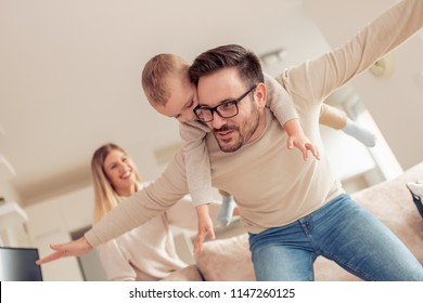 Happy family -mother, father and little son at home.