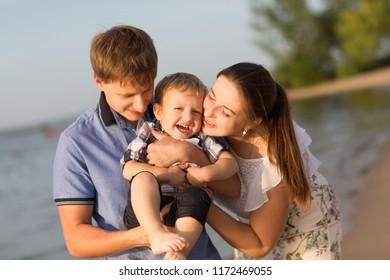 happy family mother, father and little child Having Fun outdoors in summer