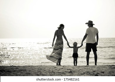 Happy family mother father and little son on sandy beach having fun