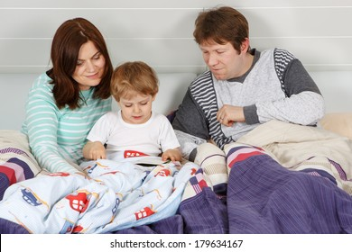 Happy family: Mother, father and little son reading book before going to bed