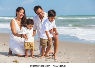 A happy family of mother, father parents & two boy son children, playng and having fun in the sand of a sunny beach