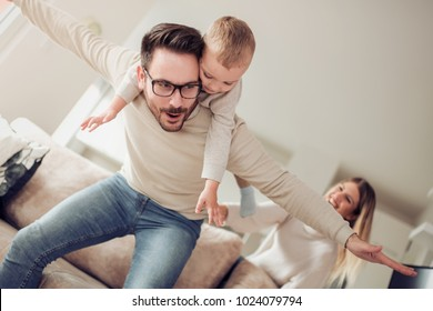 Happy family, mother and father playing with a son at home.
