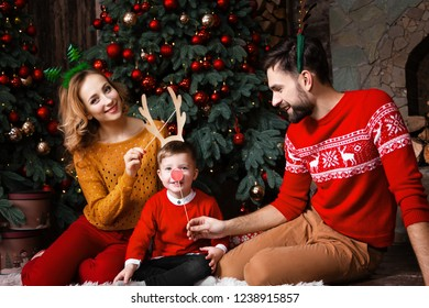 Happy family: mother, father and son child wear decorating deer horns and green christmas tree on head near decorated christmas tree at home during winter holidays. Merry Christmas and Happy New Year