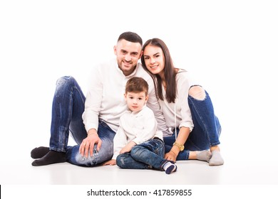 happy family mother, father and son sitting on the floor on white