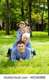 Happy family: mother, father, son and daughters-twins in the park on a sunny summer day
