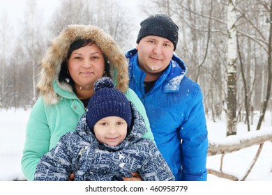 Happy family (mother, father, son) pose during snowfall in winter day, focus on boy