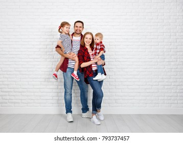 Happy family mother, father, son, daughter on a white blank brick wall background
