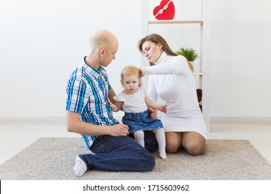 Happy family, mother, father and their baby together in living room at home. Children and toddler concept.