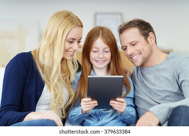 Happy family of Mother, Father and their cute young daughter sitting on a couch sharing a tablet computer with smiles of pleasure