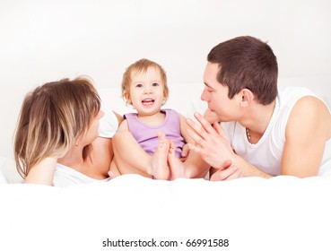 happy family, mother ,father and their baby on the bed at home (focus on the baby)