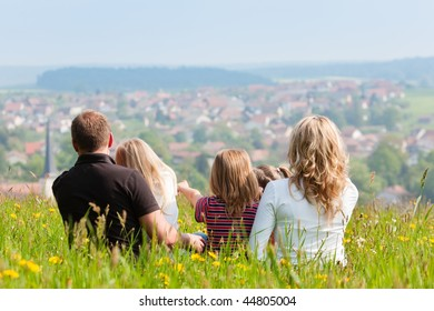 Happy family - mother, father, three children - sitting in a meadow in spring  or early summer, looking over the countryside, a village is to be seen
