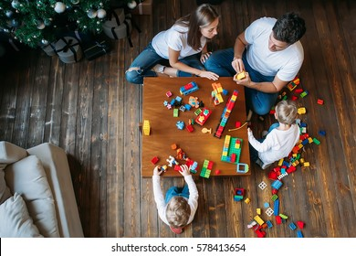 happy family mother father twins boys playing with constructor at home on table