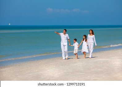 Happy family of mother, father and two children, son and daughter, walking holding hands and having fun in the sand on a sunny beach