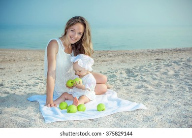 Happy family. Mother and her daughter having fun on the beach. With green apples. Positive human emotions, feelings.