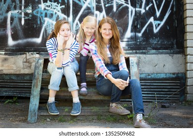happy family - a mother and her daughters sit on the background of the wall with graffiti