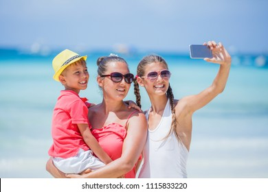 Happy family - mother and her kids making selfie and having fun at the tropical beach