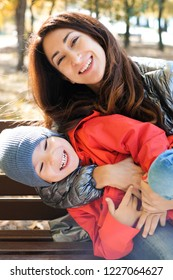 Happy family mother and her son playing and laughing on autumn walk. Warm sunny weather.