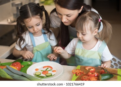 happy family mother and kids daughters are preparing healthy food, they improvise together in the kitchen