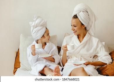 glückliche Familienmutter und kleine Tochter in Bademantel und Handtücher zu Hause und entspannen Sie sich mit einem Pokal Kaffee im Bett