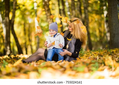 Happy family mother playing with child in autumn park near tree lying on yellow leaves