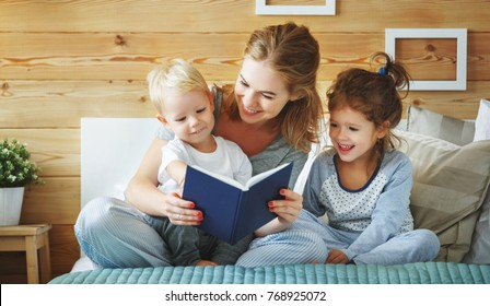 happy family mother reading to   children book in bed