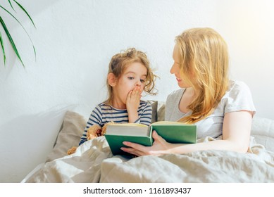happy family mother reading to daughter in bed. wonderful world of books for children. Acquaintance of the child with reading.