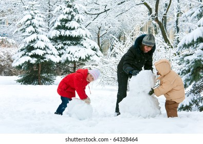 Happy family (mother with small boy and girl) in winter city park. Beautiful natural winter walking and playing with children concept.