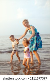Happy family mother, son and daughter playing on the beach near the sea. Woman, boy and girl have fun