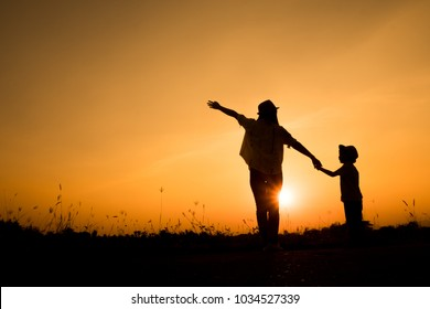 Happy family. A mother and son playing in grass fields outdoors at evening silhouette.Vintage Tone and copy space