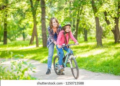 Happy family. Mother teaches her daughter to ride a bicycle in the park