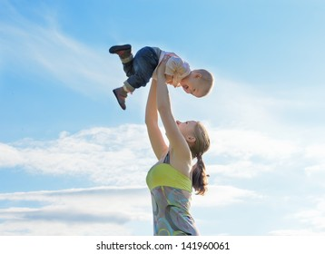 happy family. Mother throws up  baby in the sky in nature