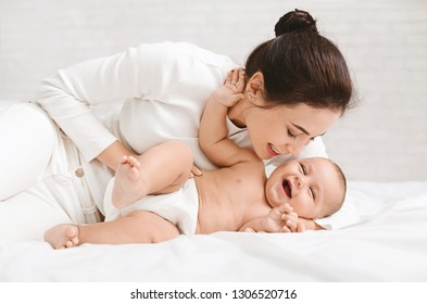 Happy family. Mother tickling her laughing baby, playing in bed at home
