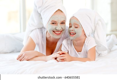 Happy family mother and toddler make face skin  mask with towel on head