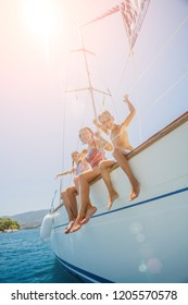 Happy family - mother with two kids having fun and jumping in sea of sailing yacht on summer cruise. Travel adventure, yachting with child on family vacation.