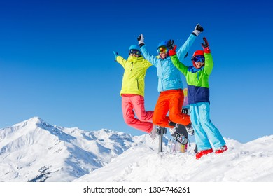 Happy family - mother and two kids enjoying winter vacations in mountains . Ski, Sun, Snow and fun.
