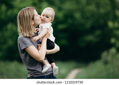 Happy family, motherhood and lifestyle concept. Loving mom kissing her baby girl outdoors. Mother and daughter