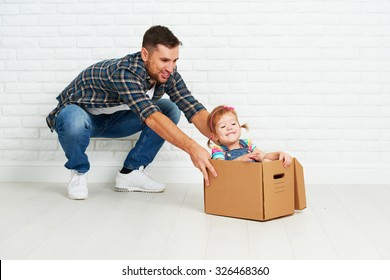 happy family moves to new apartment. dad and child  daughter playing  and have fun packs in cardboard boxes