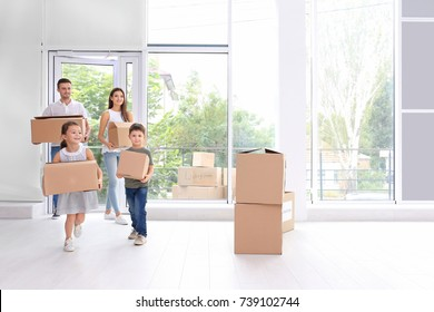 Happy family with moving boxes entering new house